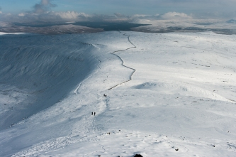 The zig-zag of the wall stands out in the snow below Ingleborough summit