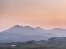 A pink and orange sunrise over Scafell and Scafell Pike seen from the south