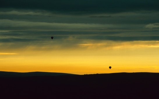 Two balloons rise and fall with the landscape at sunset near Skipton