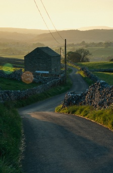 A single track roads winds between dry stone walls near Grassington