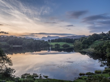 The sunset is reflected in Loughrigg Tarn with the distinctive Langdale skyline behind.