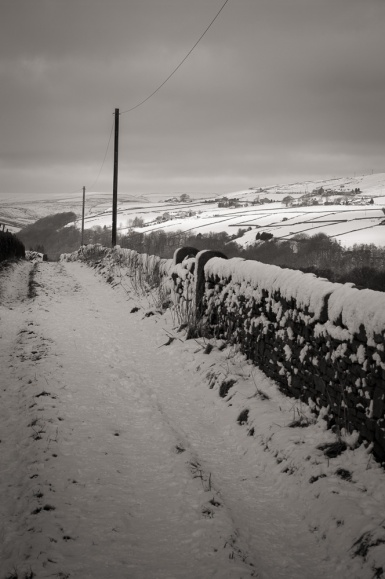Looking along a snowy lane into the hills behind Heptonstall